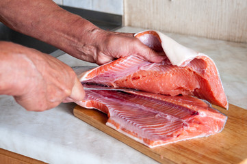 Woman is cutting red fish in the kitchen