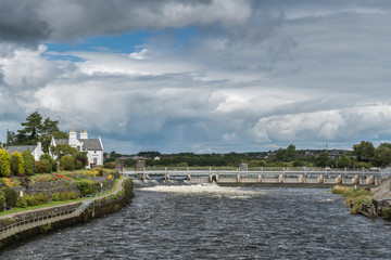 Galway, Ireland - August 5, 2017: Speed and volume of the fast flowing Corrib River is controlled by a dam system with floodgates upstream of the city. Cloudscape, trees, white water and 1899 office.