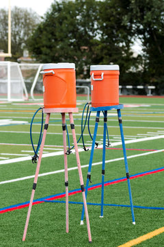 Two orange water coolers on stands for athletes
