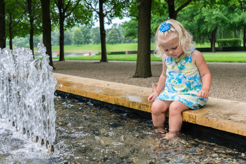 Little blonde girl dangling her feet in a fountain at the park