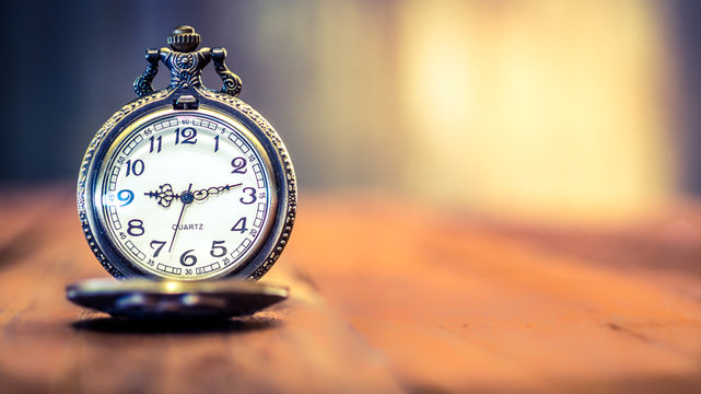 old antique pocket watch showing time on wooden floor with blurred background