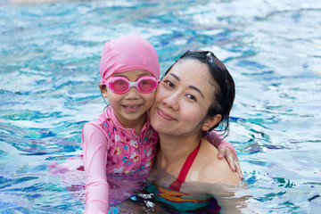 Smiling beautiful woman and little girl in a swimming pool