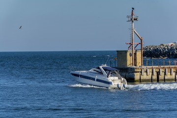 Luxury yacht leaving port of Tomis, Constanta. White cabin cruiser over blue water. Luxury motor boat  in navigation
