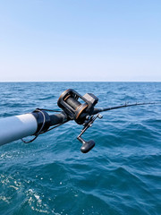 fishing pole with reel over Lake Michigan water with sky horizon