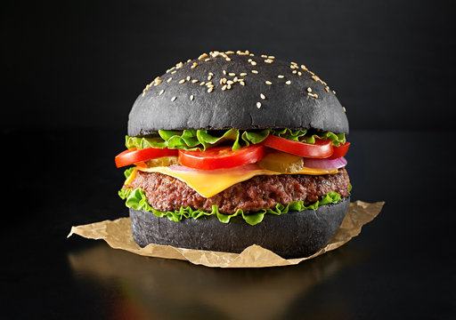 One black burger isolated on black background. Above view.