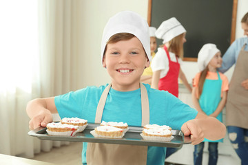 Boy holding tray with delicious cakes prepared during cooking classes