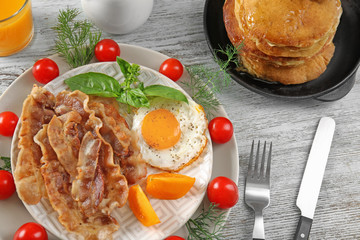 Tasty breakfast with fried egg, bacon and pancakes on table
