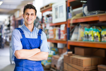 Portrait of cheerful man in uniform on his workplace in building store.