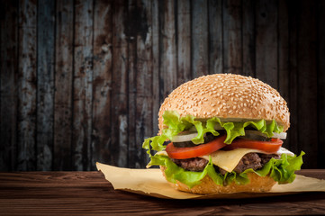 Fototapeta Delicious cheeseburger with salad ingredients on a grilled beef patty on a rustic wooden table with copyspace obraz