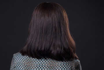 Demonstration of hairstyles Bob cut on an isolated black background rear view