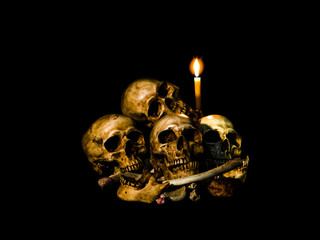 Human skulls and pile bone with candle Light. Isolated on dark background with clipping path