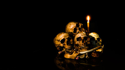 The visual art still life image of human skulls and pile bone with candle Light