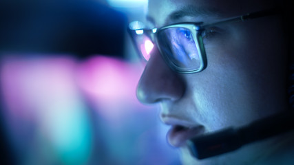 Close-up of Teenager Wearing Glasses Playing Video Games in His Headset Giving Commands into Microphone.