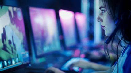 Progamer Girl Playing in MMORPG/ Strategy Video Game and Participating in Online Cyber Games Tournament or Playing in Internet Cafe.