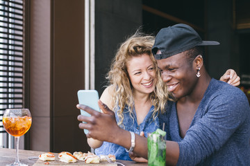 Loving couple watching the smartphone during aperitif in a local