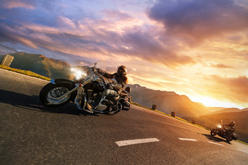 Motorcycle drivers riding in Alpine highway. Outdoor photography, mountain landscape.