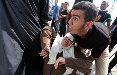 A Palestinian woman is helped after falling on the ground during an attempt to block the convoy of U.N. Secretary General Guterres upon his arrival near Erez crossing in the northern Gaza Strip