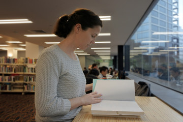Female student reading a book in a library