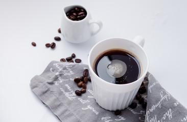 Kaffeetasse mit Bohnen auf einem weißen Tisch