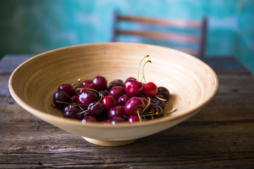 Cherry in a wooden plate in rustic style