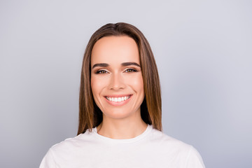 Close up portrait of successful young brown haired lady entrepreneur in white casual t shirt, standing on the pure light grey background, with beaming smile Wall mural