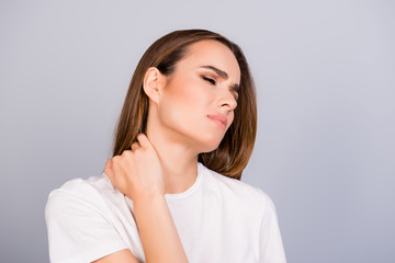 Young frustrated brown haired lady is having a strong pain in neck. She is in a white tshirt, massaging the neck, with pain grimace Wall mural