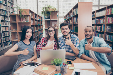 We like education! Successful future for smart youth! Four attractive young bachelors are welcoming in their university`s library, gesturing thumbups, smiling, wearing casual smart