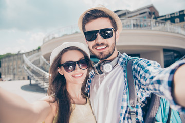 Close up of a cheerful young couple making selfie photo on camera. They are in tourist`s outfits, caps, eyewear, posing and smiling outdoors on a sunny vacation