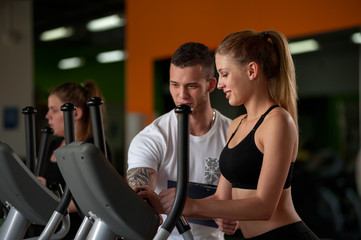 Blonde woman working out with fitness coach in gym