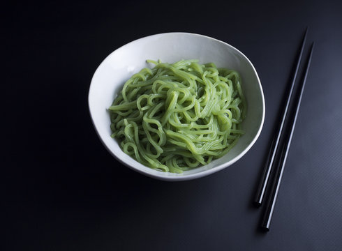 Japanese konjac noodles with spinach in rustic bowl and chopsticks on the side, isolated on black background