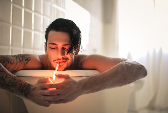 Attractive guy relaxing in the bathtub while smocking a cigarette