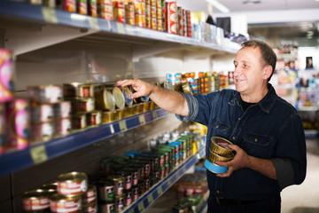 Pensioner selecting preserves at store