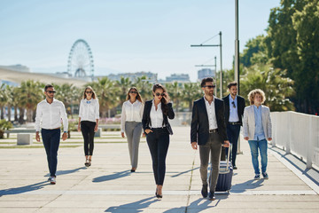 People in official clothes walking together on business trip