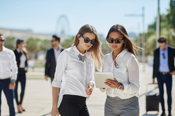 Two pretty  businesswomen using tablet on business trip
