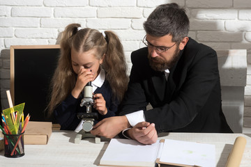 Girl and man sit by desk and looks into microscope
