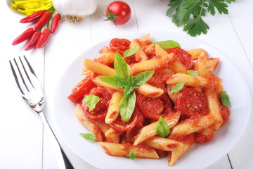 Pasta, penne with tomato sauce and basil