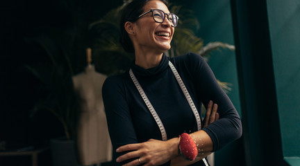 Female fashion designer laughing in her studio