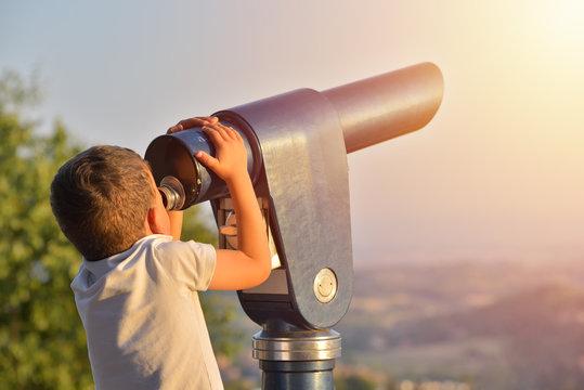 Little boy looking into tourist telescope eyepiece. Travel tourist destination landscape magnification