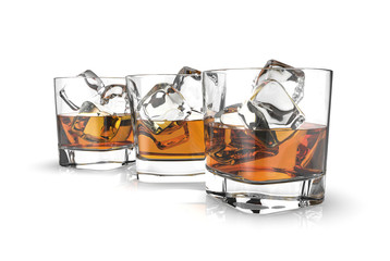 Three glasses of whiskey with ice cubes isolated on a white background.