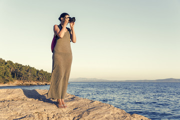 Young woman photographer on a rocky seashore on evening.