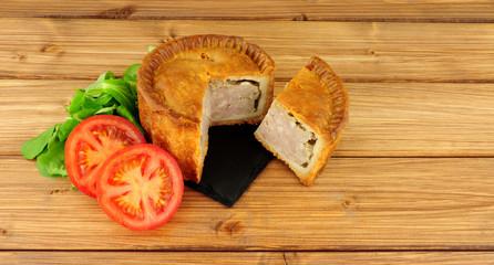 Crusty savoury pork pie on a wood background