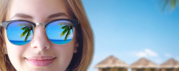 Beautiful young girl in the sunglasses in the sea background.