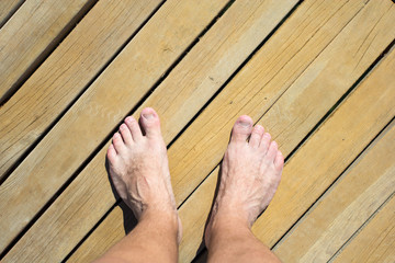 male legs over wooden beach road