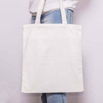 Girl in blue jeans holds blank cotton eco tote bag, design mockup. Handmade shopping bag for girls
