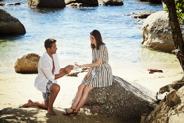 Handsome man proposing to beautiful wife to be on beach