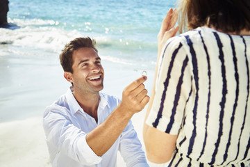 Handsome fellow proposing to partner with wedding ring, smiling