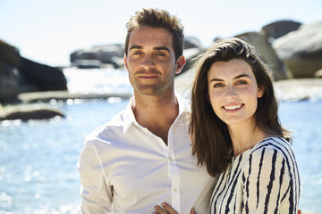 Perfect couple smiling on beach with sea behind, portrait