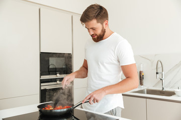 Side view of pleased bearded man cooking