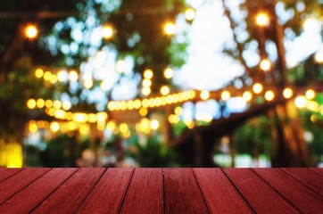 empty wooden desk, terrace or floor copy space for display of product or object presentation with blurred image of abstract night light bokeh of night festival in garden background, vintage tone