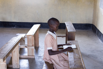 School girl studying alone in classroom. Kenya, Africa.